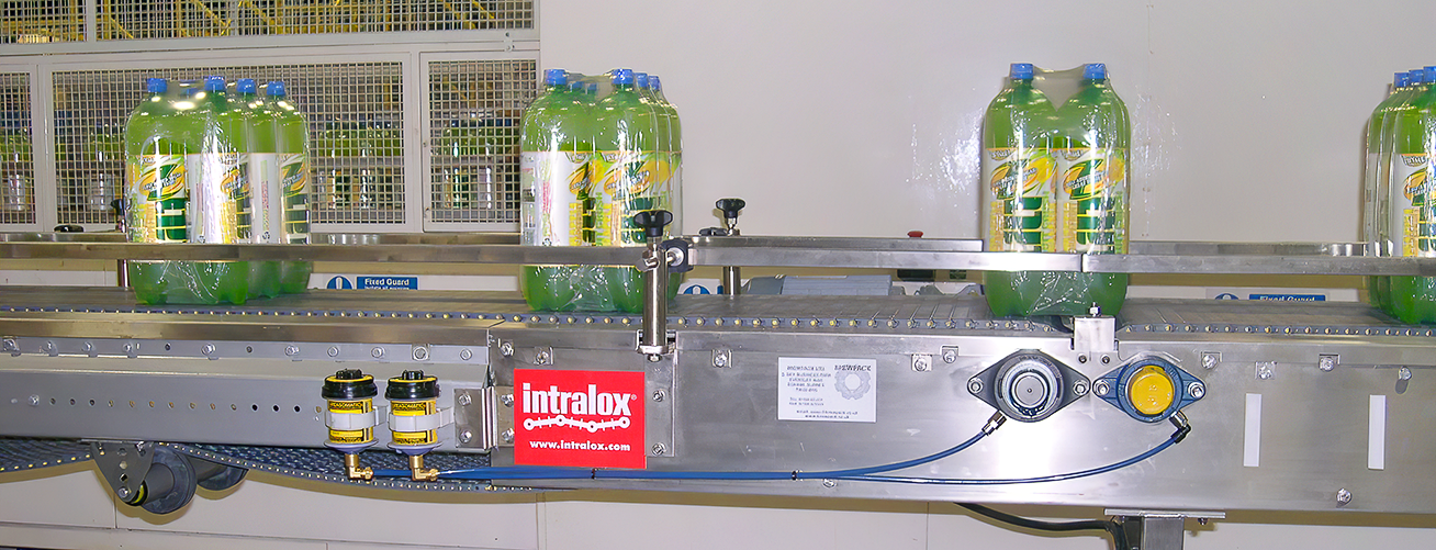 Greasomatics with FM grade grease lubricate bottling conveyors.